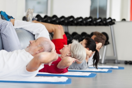 daughter in law: Side view of family with fitness ball practicing crunches in gym