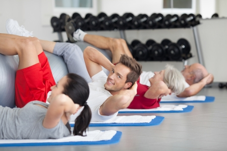 toning: Handsome young man doing a fitness course training in a gym doing head lifts with a group of diverse people