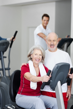 hometrainer: Active attractive senior couple training in a gym working out on the equipment posing and smiling at the camera Stock Photo