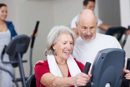 Smiling happy senior woman working out at the gym supported by her affectionate husband who is watching the display on the equipment with her photo