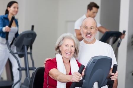 Portrait of happy senior couple with using treadmill in background at gym photo