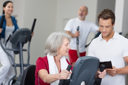 Senior woman with a handsome male personal fitness trainer working out in a gym while he notes her progress on a clipboard