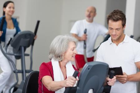 actividad fisica: Mujer mayor con un apuesto hombre entrenador personal de trabajo en un gimnasio mientras él observa su progreso en un portapapeles