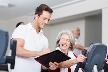 Trainer stimuleren van een hooggeplaatste vrouw op de sportschool met haar een grafiek van haar vorderingen op een klembord als ze werkt op het materieel Stockfoto