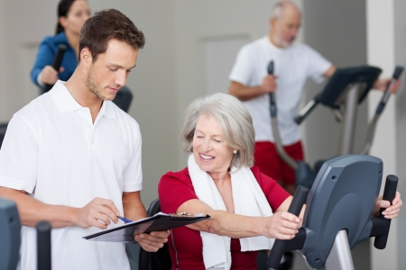 Male instructor explaining schedule to senior woman using rowing machine in gym