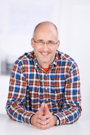 middle joint: Ritratto di uomo d'affari fiducioso sorridente alla scrivania in ufficio