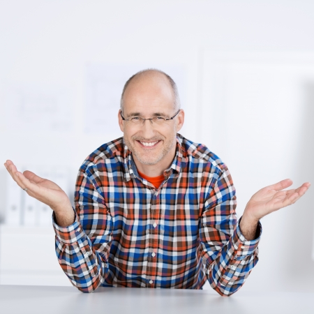 Portrait of a smiling mature balding caucasian man wearing glasses, sitting at a table and raising his hands in the air photo