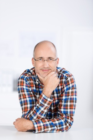 chin on hands: Portrait of a smiling mature balding caucasian man wearing glasses, sitting at a table and holding his chin with the hand