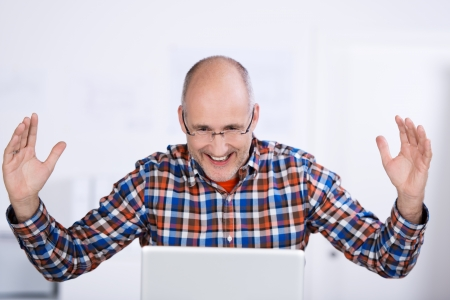 exuberant: Portrait of a smiling mature balding caucasian man wearing glasses, sitting at a table and raising arms in joy and happiness while looking at a laptop screen