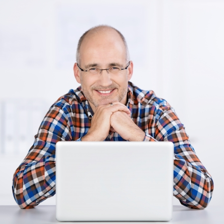 looking behind: Portrait of a friendly smiling mature balding caucasian man, wearing glasses, sitting at a table behind a laptop computer and holding the chin with both hands Stock Photo