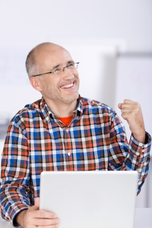Happy businessman with clenched fist looking away in office photo