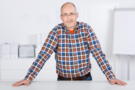 man behind: Portrait of a smiling mature balding caucasian man, wearing glasses, standing and leaning over a desk in the office