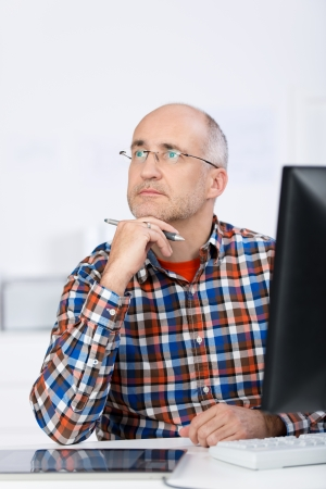 Portrait of a mature balding caucasian man wearing glasses, sitting at the office desk, holding his chin with the hand and looking up and away in a serious and pensive mood photo