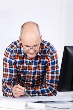 professional development: Portrait of a mature balding caucasian male engineer wearing glasses, sitting at the office desk, looking and studying plans in a pensive mood
