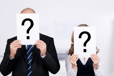 Businesspeople holding question mark signs on placard in front of faces at office photo