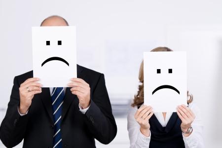 事務所で顔の前でプラカードに悲しいスマイリーを保持しているビジネスマン 写真素材