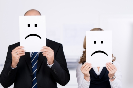 Businesspeople holding sad smileys on placard in front of faces at office