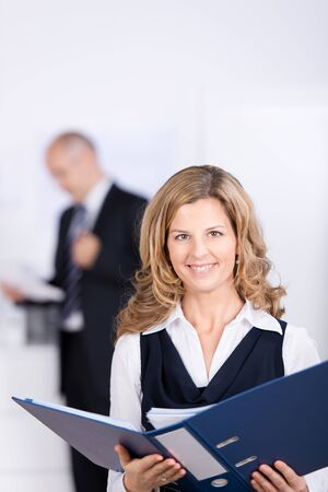 Portrait of confident businesswoman holding binder with coworker standing in background at office photo