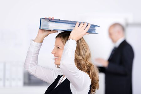 Playful beautiful young businesswoman walking through an office with a binder balanced on her head photo