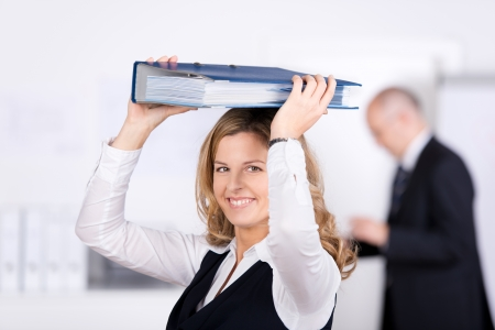 Portrait of businesswoman carrying binder on head with coworker standing in background at office photo