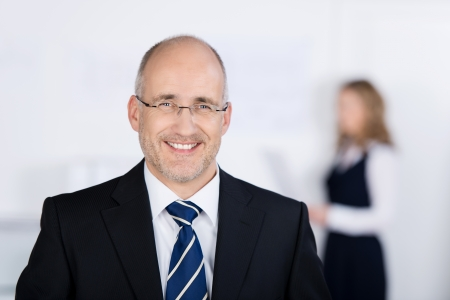 Portrait of confident businessman smiling with coworker in background at office photo