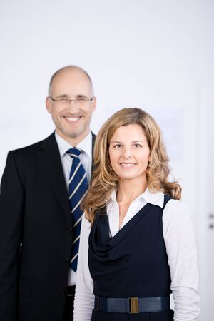 Successful team in the office with a business man and woman posing together standing and smiling at the camera photo