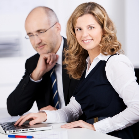 Friendly businesswoman working with a male colleague in the office looking at the camera with a lovely smile photo