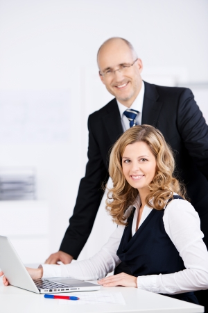 Competent dedicated business team working together in the office on a laptop computer with an attractive middle-aged businessman standing over his beautiful female colleague photo