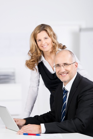 Motivated businessman and woman working together as a successful team on a laptop computer at a desk in the office looking at the camera with friendly smiles photo