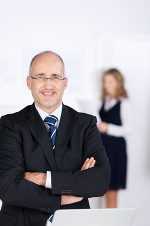 Portrait of confident businessman with arms crossed standing in office photo