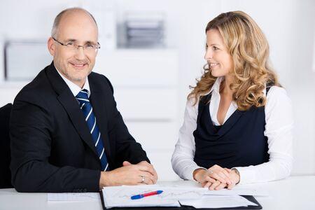 amigas conversando: Dos compañeros de trabajo, un hombre de negocios de mediana edad y una mujer, tener una reunión sentado en una mesa en la oficina de examinar los documentos