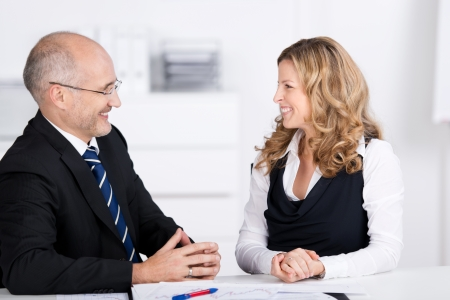 conversing: Happy businesspeople conversing while looking at each other at desk in office Stock Photo