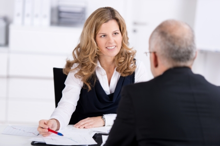 Personnel manager conducting a corporate job interview questioning the applicant on his experience, qualifications and curriculum vitae, over the shoulder view Stock Photo