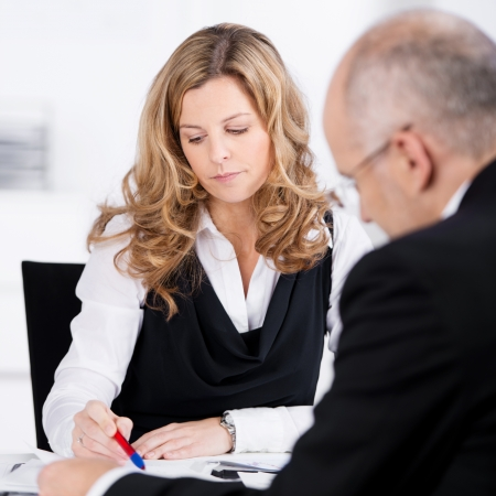 Two businesspeople or partners having a serious discussion with an over the shoulder view of the woman pointing out details in a document to her male colleague photo