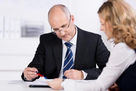 Dos colegas de negocios que tienen una reunión sentados juntos en un escritorio en la oficina de discutir un documento con enfoque a un atractivo hombre calvo de mediana edad Foto de archivo