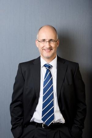 Portret van een lachende en ontspannen volwassen kalende zakenman, het dragen van een pak en een stropdas, met de handen in de zakken, in voor een grijze muur