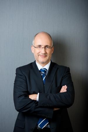 Portret van een glimlachende en zelfverzekerde volwassen kalende zakenman, het dragen van een pak en een stropdas, met de armen gekruist, voor een grijze muur Stockfoto