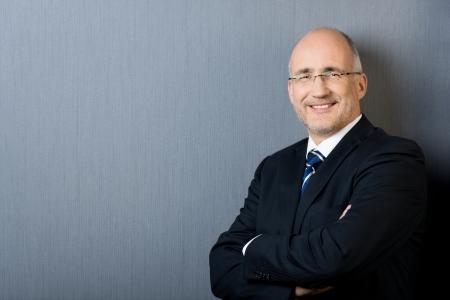 Profiel portret van een glimlachende en zelfverzekerde volwassen kalende zakenman, het dragen van een pak en een stropdas, met de armen gekruist, voor een grijze muur met exemplaar-ruimte