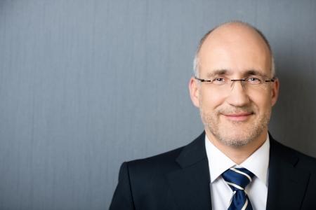 Close-up portret van een lachende vriendelijke oudere kalende zakenman, het dragen van een pak en een stropdas, leunend tegen een grijze muur met exemplaar-ruimte Stockfoto