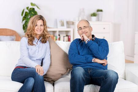 Portrait of couple smiling while sitting on sofa at home photo