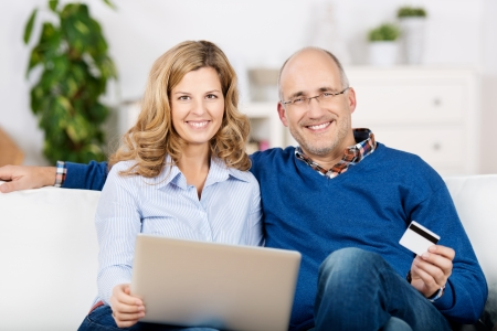 online banking: Portrait of happy couple using laptop and credit card for online shopping while sitting on sofa Stock Photo