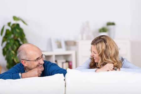 View from behind of a smiling playful couple relaxing on a sofa peeking their heads over the top of the cushions and laughing at each other photo