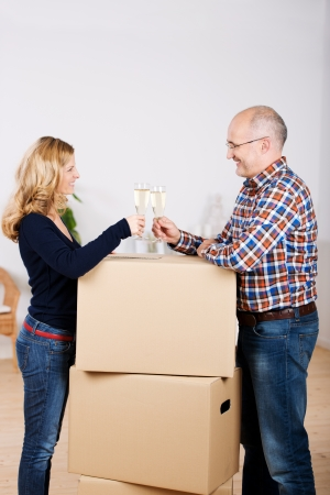 Happy couple toasting champagne flutes while standing by stacked cardboard boxes at new home photo