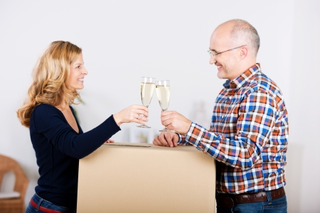 removals: Happy attractive mature couple celebrating the move to a new house toasting each other with champagne over the top of a brown cardboard carton with a smile Stock Photo