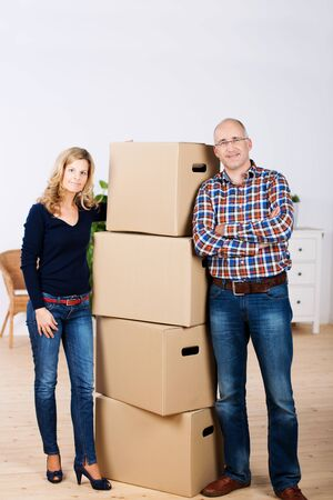 removals: Portrait of confident couple standing by stacked cardboard boxes at new home Stock Photo