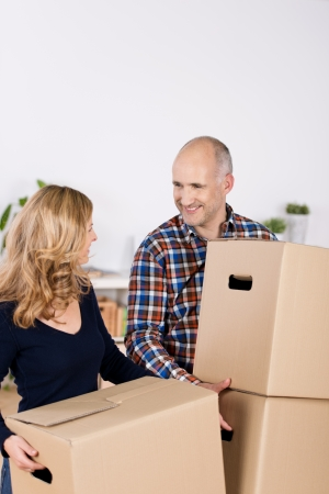 relocating: Happy couple carrying cardboard boxes while looking at each other in new home Stock Photo
