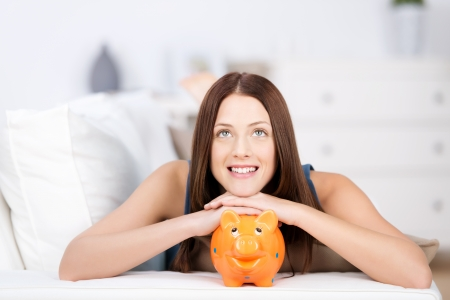 thrift box: Portrait of smiling woman daydreaming on bed with piggy bank
