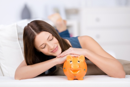 Beautiful long hair female on bed looking at the piggybank photo