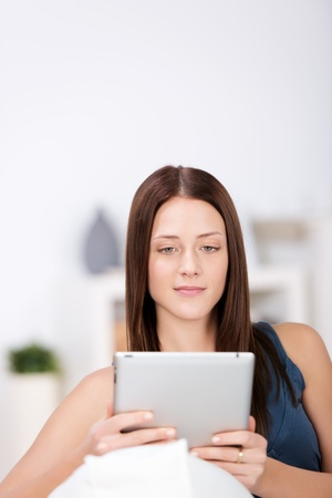 Woman sitting on the couch and surfing the internet in her ipad touch Stock Photo - 21341154