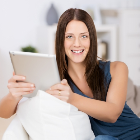 Beautiful lady sitting on the couch and browsing through ipad touch Stock Photo - 21341156